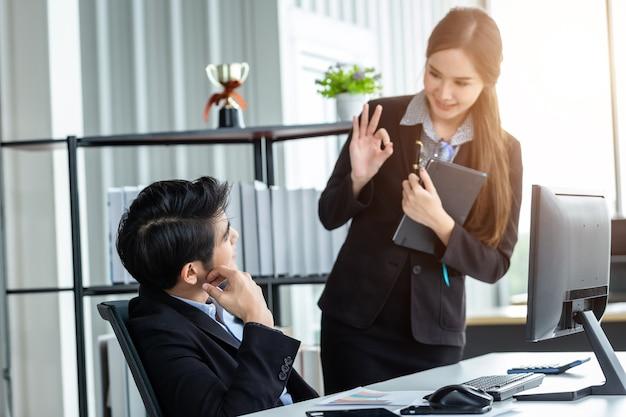 사업가 파트너와 함께 일하는 스트레스를 받는 사업가는 긍정적인 추천을 돕고 사무실 배경에서 회의할 때 컴퓨터 아이디어로 작업하도록 서로 격려합니다.