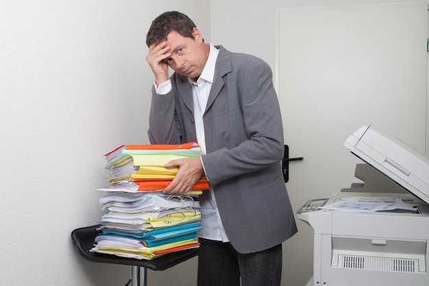 Stressed businessman in front of stack of folders at copy machine