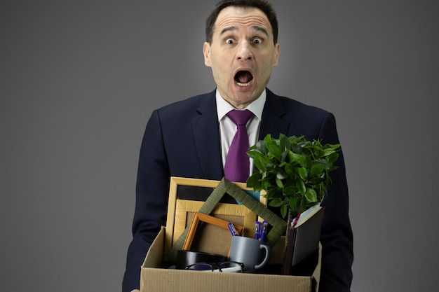 Stressed businessman holding box with his stuff. dismissed worker getting fired