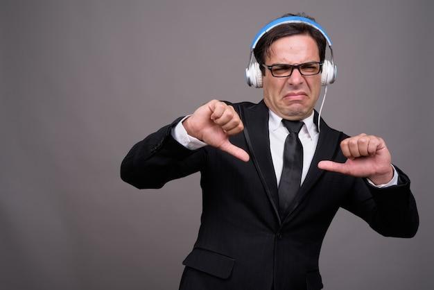 音楽を聴くと親指を下に与えるビジネスマンを強調