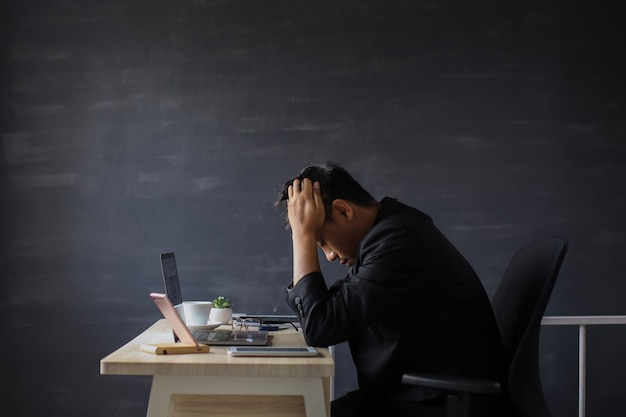 Stressed businessman pulling his hair out while sitting on his working place in office