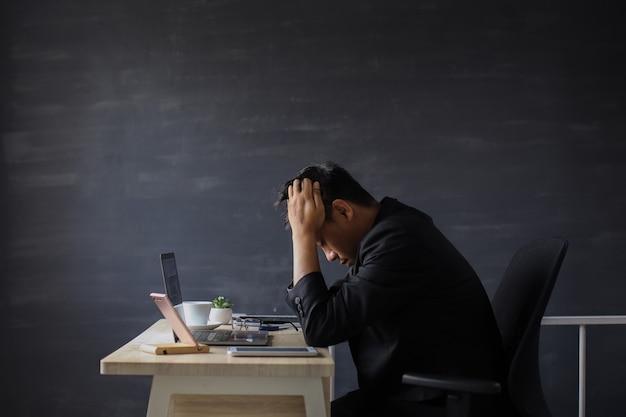 스트레스를 받는 사업가는 사무실에서 작업장에 앉아 머리를 뽑고 있다