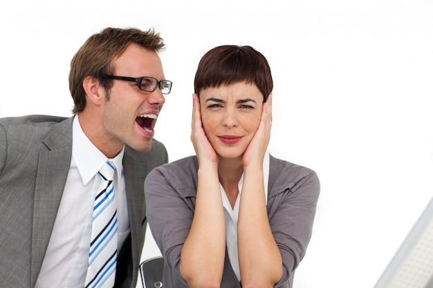 彼の同僚の耳に叫んだストレスを受けたビジネスマン