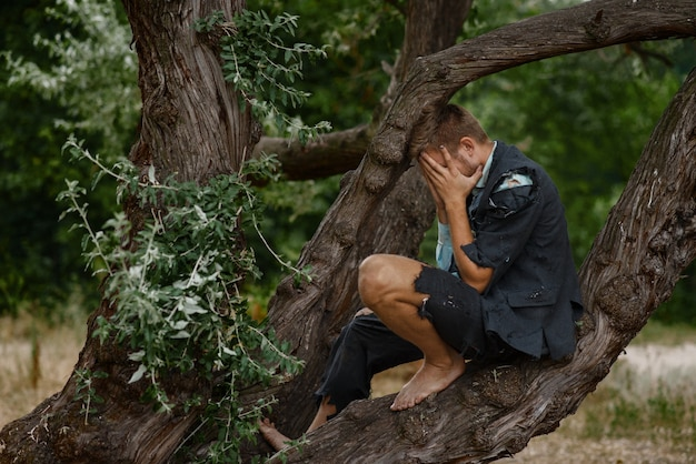 Stressed businessman in torn suit sitting on the tree on desert island.
