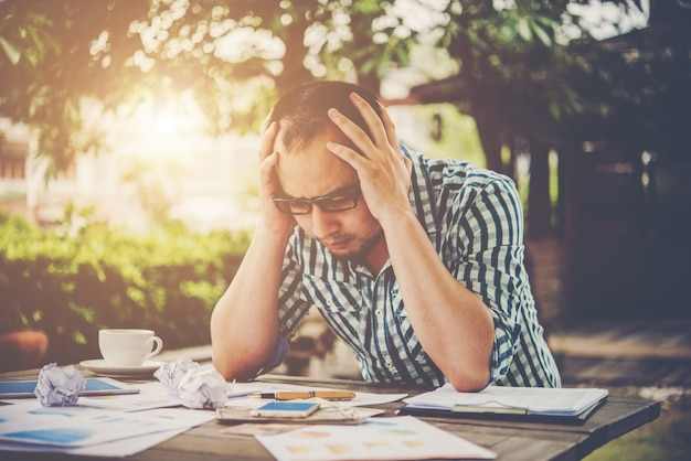 Stressed businessman with papers and charts sitting at table at home. businessman with paperwork and deadline concept.