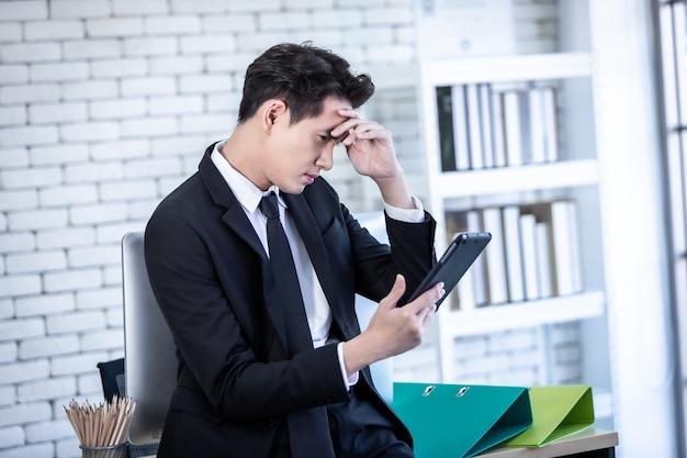 스트레스를 받는 사업가는 태블릿으로 일하고 사업 손실 후 두통을 앓고 있습니다. 사무실 배경.