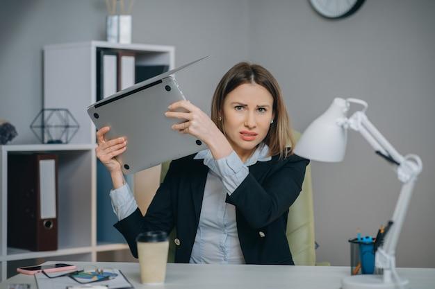 ラップトップを使用してイライラした実業家を強調し、データの損失、オンラインの間違い、ソフトウェアエラー、またはシステム障害でイライラしたコンピューターの問題に腹を立てて怒っている女性。