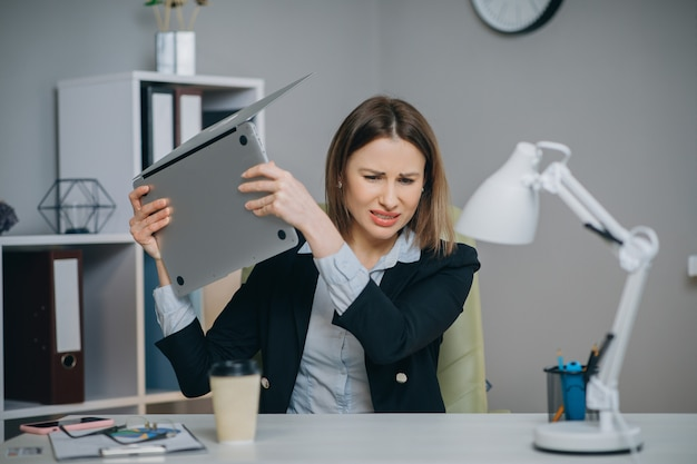 Stressed businesswoman annoyed using laptop, angry woman mad about computer problem frustrated with data loss, online mistake, software error or system failure.