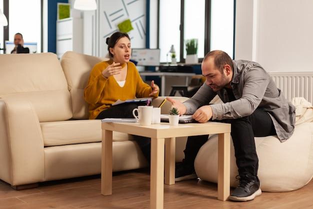 Подчеркнутая деловая женщина спорит, ругает мужчину в рабочее время, сидя на диване, в то время как разные коллеги работают напуганными на заднем плане