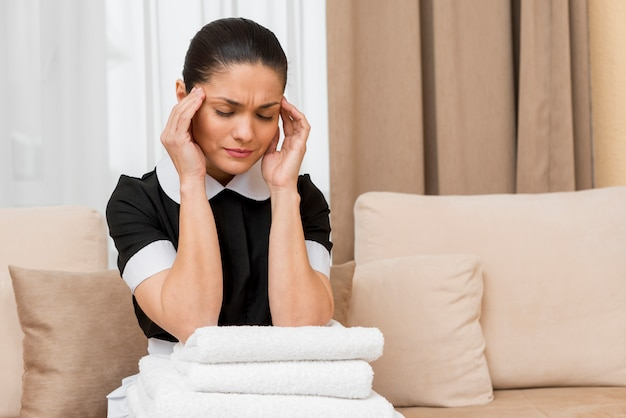 Stressed chambermaid in hotel room
