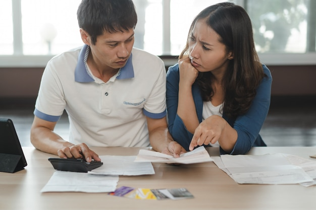 Stressed couple calculating credit card debt.