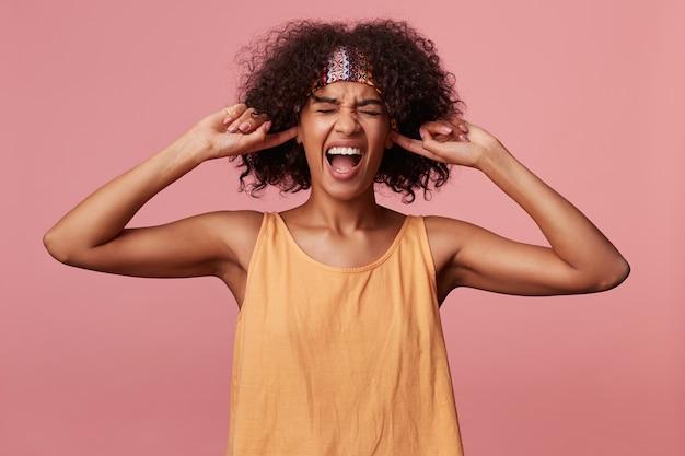 Sottolineato donna bruna riccia dalla pelle scura con taglio di capelli corto che copre le orecchie e urla con la bocca larga aperta, faccia accigliata con gli occhi chiusi mentre è in piedi
