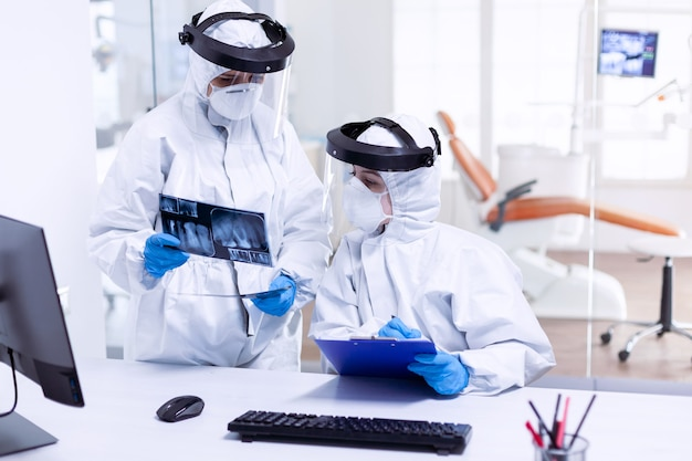 Stressed dentist and nurse examining teeth x-ray wearing ppe suit. medical specialist wearing protective gear against coronavirus during global outbreak looking at radiography in dental office.