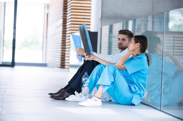 Stressed doctor and nurse sitting on floor examining x-ray report