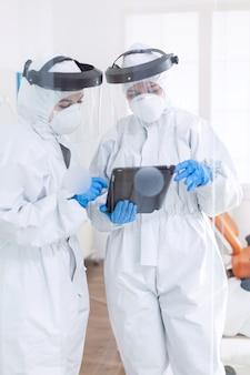 Подчеркнутые врачи, одетые в костюм ppe, используют планшетный пк бригада стоматологов в стоматологическом кабинете носит защитный костюм от заразного коронавируса во время глобальной пандемии.