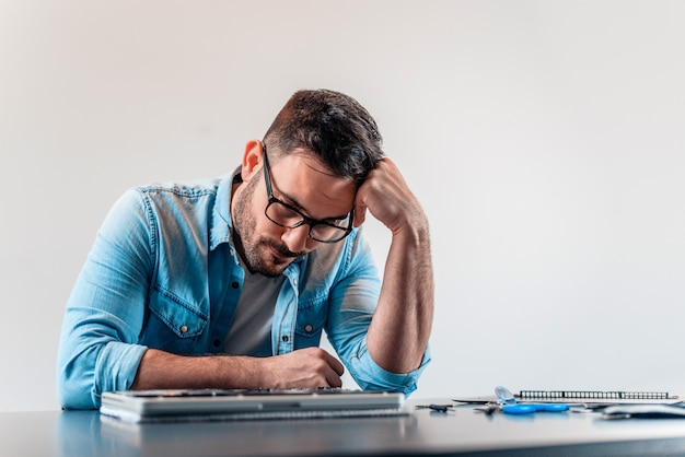 Stressed engineer can't fix problem with laptop computer hardware.