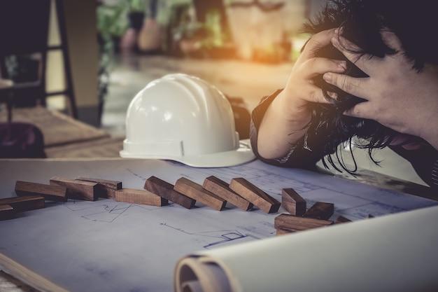 스트레스 엔지니어링은 청사진과 헬멧으로 떨어졌습니다. 한 젊은 남자가 그의 책상에 앉아 그의 손을 그의 머리에 보유합니다.