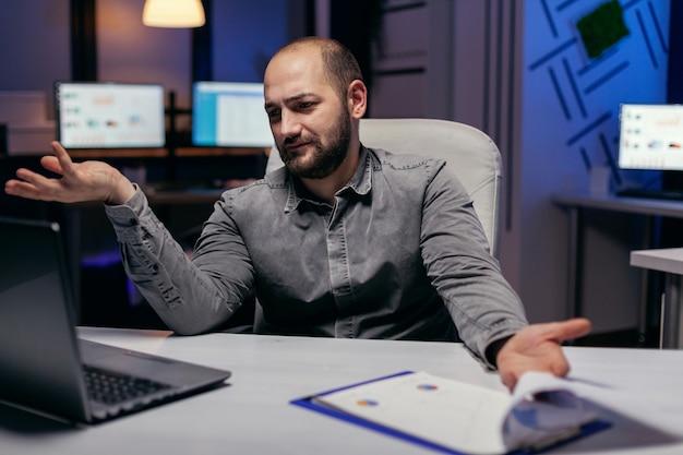 과로하는 과정에서 노트북을 보고 혼란스러워하는 스트레스를 받는 기업가. 회사의 큰 프로젝트를 완료하기 위해 초과 근무를 하는 동안 혼란스러운 사업가.