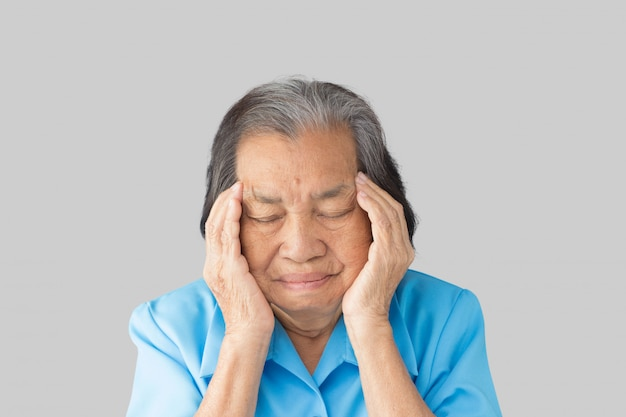 Stressed exhausted grandmother having strong tension headache on a gray background