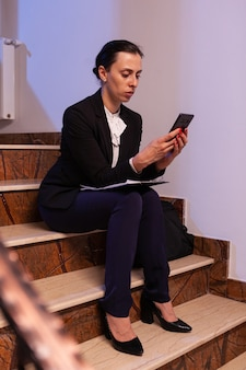 Stressed exhausted overworked businesswoman working on job deadling using smartphone overtime seriou...