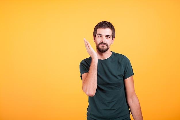 オレンジ色の背景の顔に彼の手で表現力豊かな男を強調