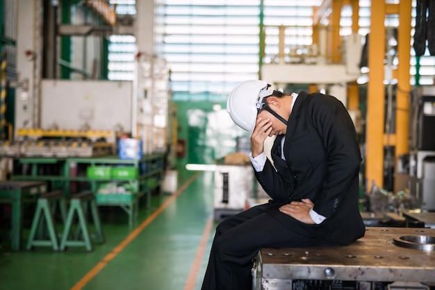 ヘルメットをかぶった工場のマネージャーまたはビジネスマンの所有者がマシンに座っていることを強調