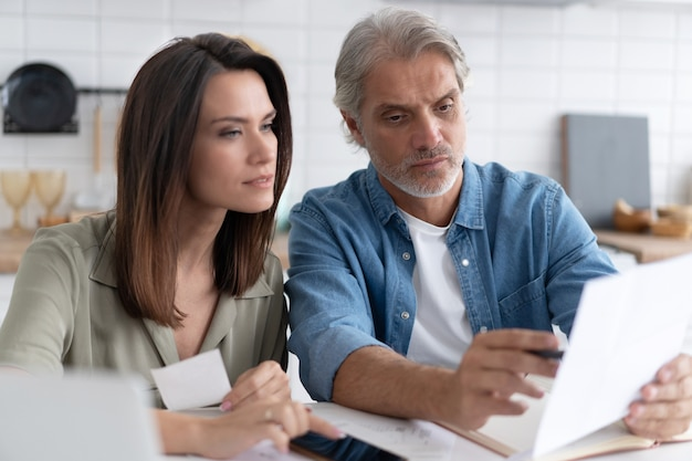 Stressed family couple feeling disappointed by high utility bills, money loss. unhappy nervous married spouse received debt mortgage notification, checking financial documents.