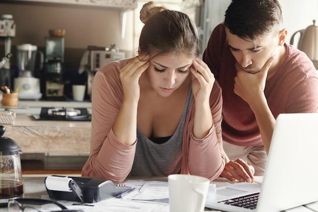 ストレスのたまった女性は、金融危機の緊張に耐えられず、寺院を圧迫し、紙幣の山、ノートパソコン、電卓を備えた台所のテーブルに座っています。解決策を見つけようとする彼女のそばにいる夫