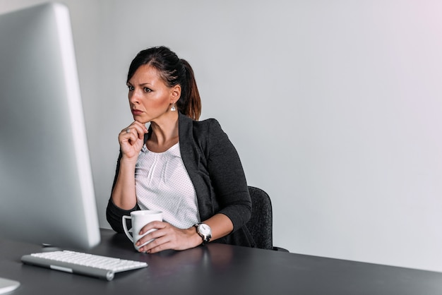 Stressed female company boss disappointed with bad news. looking at computer screen.
