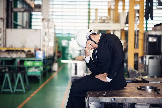 Stressed fired businessman in factory