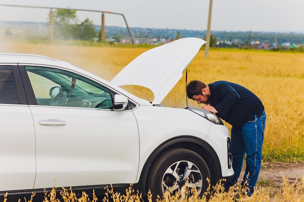 Stressed and frustrated driver pulling his hair while standing on the road next to broken car. road trip problems and assistance concepts. smoke.