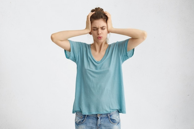 Подчеркнутая разочарованная молодая самка закрывает уши руками и закрывает глаза из-за шума