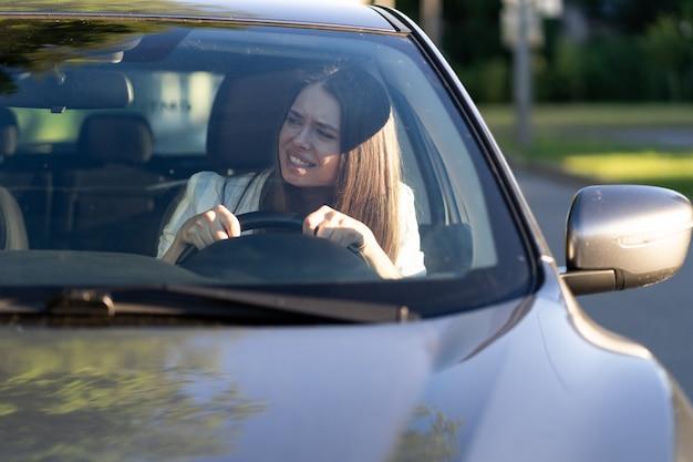 스트레스를 받은 소녀는 처음으로 차를 몰고 자동차 사고를 피하려고 매우 긴장하고 무서워합니다
