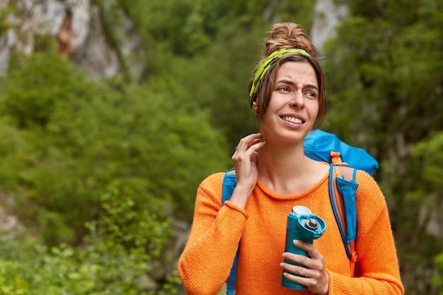 ストレスのたまった女の子の旅行者は森で迷子になり、道を見つけることができず、動揺した表情を脇に見て、緑の自然の背景でポーズをとり、フラスコからお茶を飲みます