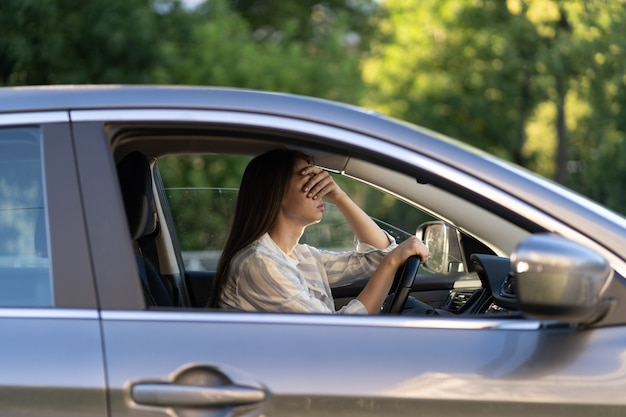 Stressed girl with headache drive car frustrated displeased young female driver suffer from illness