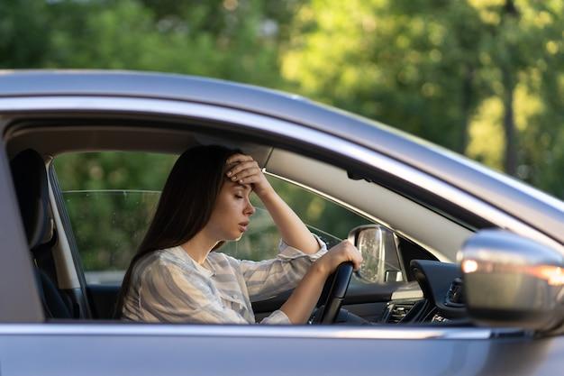 두통 운전 자동차를 가진 스트레스를 받는 소녀 좌절된 불쾌한 젊은 여성 운전자는 질병으로 고통받습니다