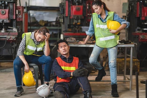 스트레스를받는 아시아 남성 및 여성 엔지니어 그룹이 산업 공장 바닥에 앉아 피곤해 보입니다.