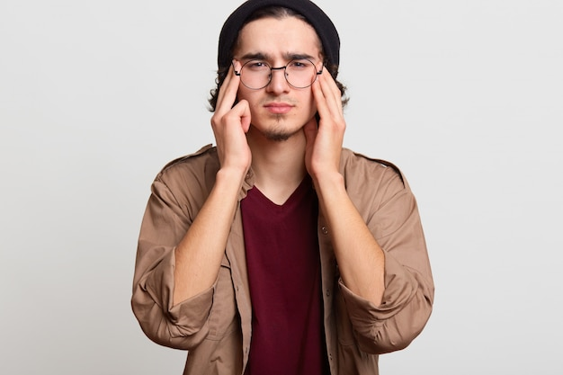 Stressed handsome youngster touching his temples with both hands, feeling headache, trying to reduce it, looks upset. black haired slim model wears black hat, red and beige shirts, spectacles.