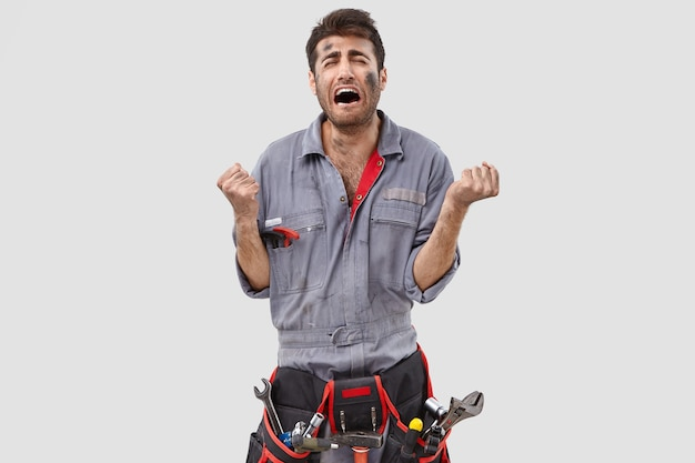 Stressed handyman posing against the white wall