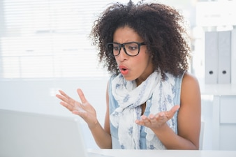 Stressed hipster working at her desk with laptop