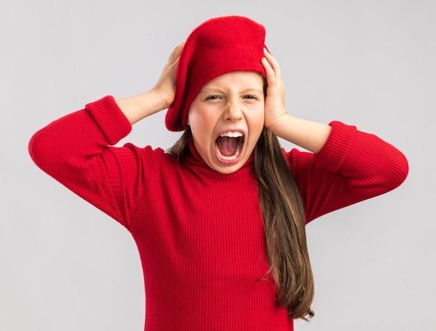 Piccola ragazza bionda stressata che indossa un berretto rosso che tiene le mani sulla testa guardando la telecamera e urlando isolata sul muro bianco