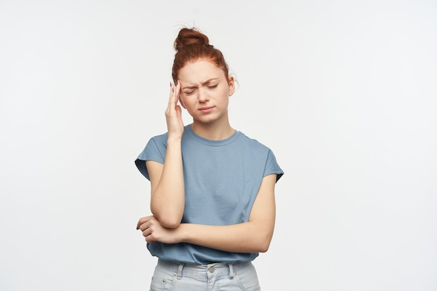 Stressed looking woman, girl with ginger hair gathered in a bun. wearing blue t-shirt and jeans. massaging her temple, suffer from migraine. stand exhausted, isolated over white wall