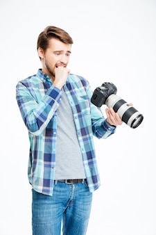 Stressed male photographer holding photo camera isolated on a white background