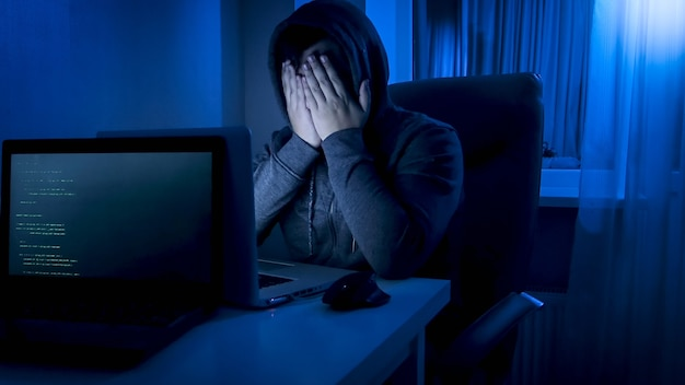 Stressed male programmer holding hands on his face while working on computer at night