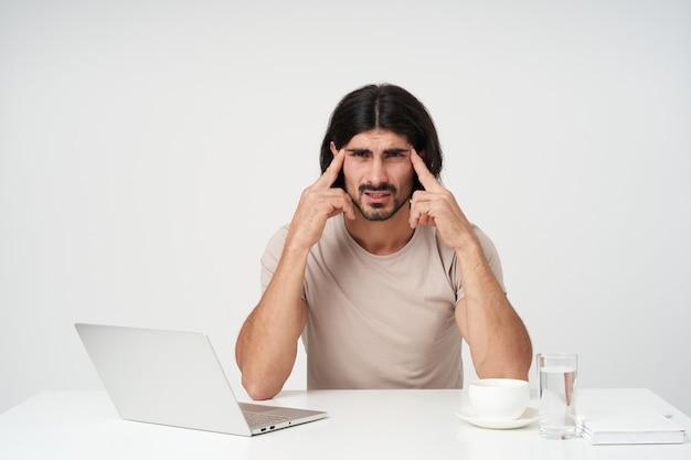 黒髪とあごひげを持つ男性、疲れたビジネスマンを強調しました。オフィスのコンセプト。職場に座っています。頭痛に苦しんでいます。こめかみのマッサージ。白い壁に隔離