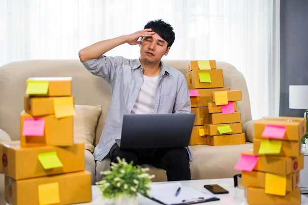 Stressed man entrepreneur working with laptop computer and has problem to selling product online at home office
