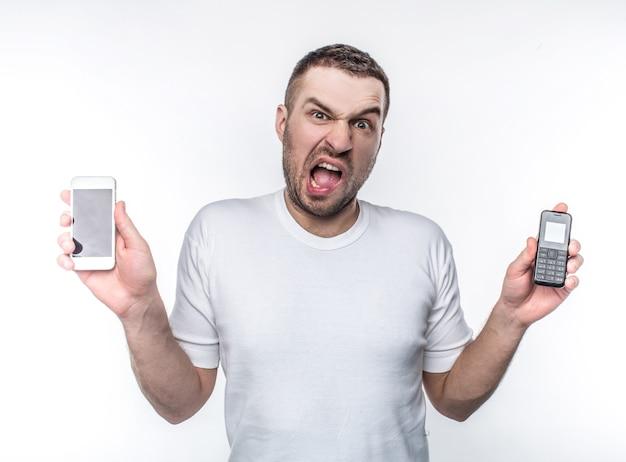 스트레스를 받는 남자는 다른 해에 만들어진 두 개의 다른 전화기를 들고 있습니다. 기술이 너무 빨리 변하기 때문에 이러한 변화는 그에게 스트레스가 됩니다. 흰색 배경에 고립