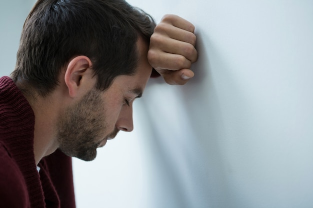 Stressed man leaning on wall