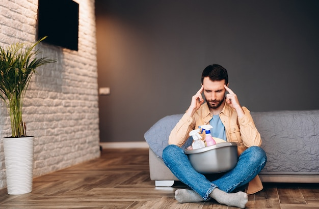 Stressed man looking disappointed before housecleaning, sitting on floor