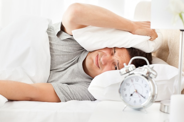 Stressed man looking at his alarm clock ringing